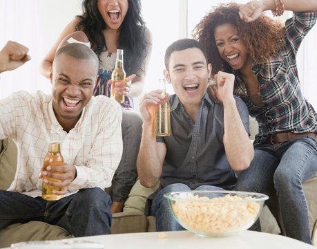Friends drinking beer and watching football on television