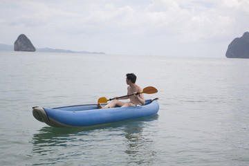 Chinese man paddling boat in ocean