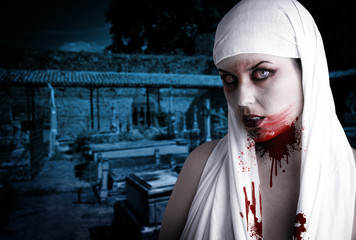 Female vampire with blood stains in a cemetery. Gothic Image hal