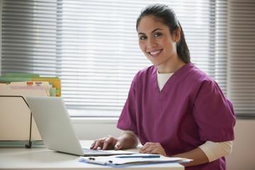 Mixed race nurse using laptop