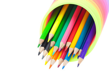 Colorful toy spring and colored pencils isolated on white