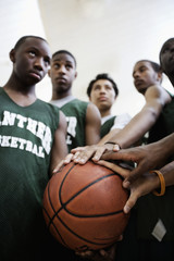 Basketball team touching ball in huddle
