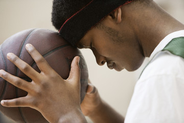 African basketball player leaning head on ball