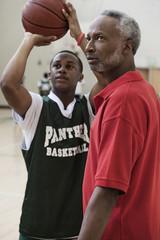 African coach watching basketball player shoot ball
