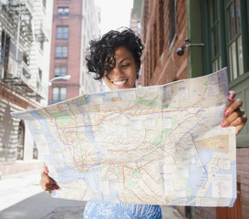 Mixed race woman holding map on urban street