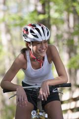 Hispanic woman sitting on bicycle