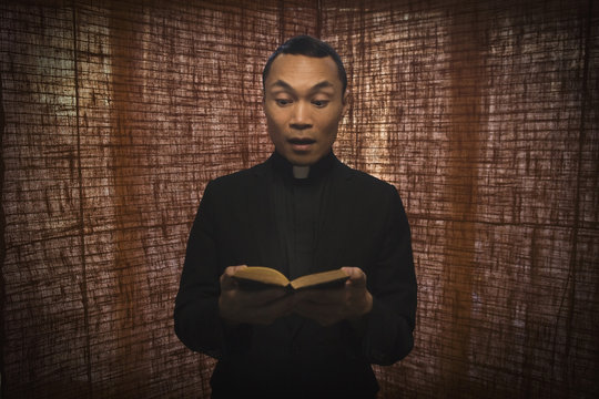 Pacific Islander priest reading bible