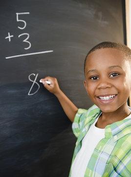 Black boy solving math problems on blackboard