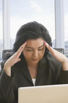 Hispanic businesswoman with headache using laptop