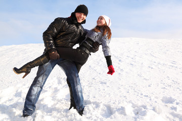 man and girl dance on snowy area and smiling