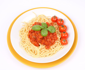 Spaghetti Bolognese on a plate with basil and cherry tomatoes