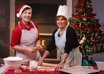 Mother and daughter baking christmas cake