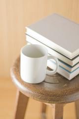 椅子の上に置かれたコップと本