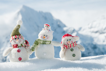 Happy snowmans in mountain