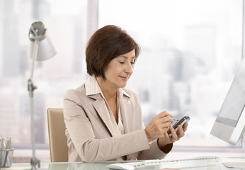 Mature female executive using smartphone in office