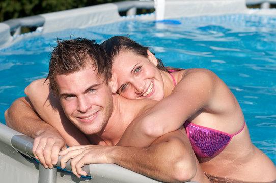 Giovane coppia si abbraccia in piscina