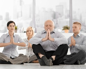 Businesspeople doing meditation in office