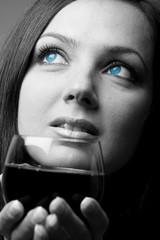 Donna pensierosa con occhi azzurri e calice di vino