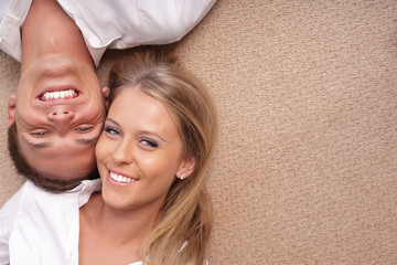 Young couple lying on the floor with their heads together
