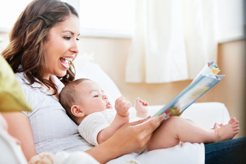 Charming mother showing images in a book to her cute little son