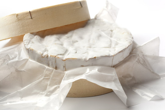 Whole Camembert cheese in a wooden box