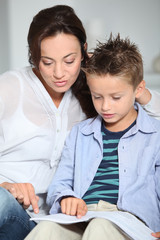 Little boy and mother sitting on sofa at home with book
