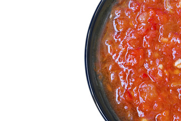Tomato sauce on the black plate isolated over white