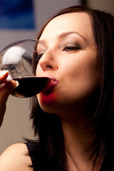 Donna che beve un calice di vino rosso
