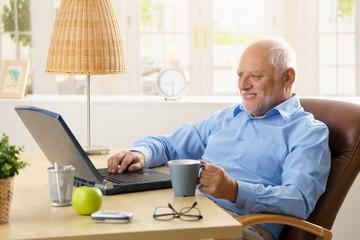 Smiling senior man using laptop