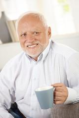 Smiling old man having coffee