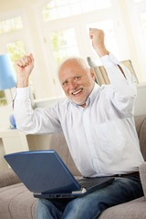 Happy old man sitting on sofa with laptop