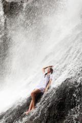 Mädchen sitzt im Wasserfall