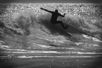 Surfer on a wave in black and white