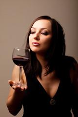 Donna che fissa un calice di vino rosso