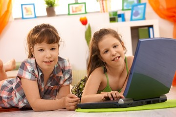 Little girls playing on computer at home