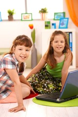 Small girls with computer at home