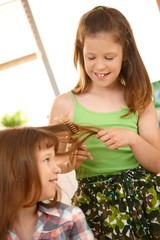 Young girls enjoying combing hair