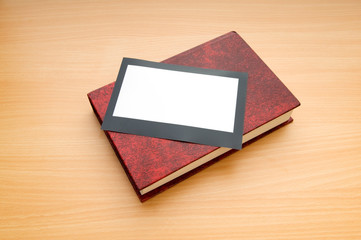Books and blank photos on wooden table