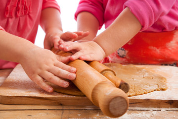 two little girls with rolling pins baking and having fun