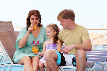 mom dad and daughter rest on deck of yacht and drink tasty juice