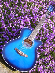 electric blue guitar on wall of purple flowers