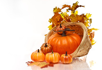 Pumpkins and Autumn leaves in a wicker basket.