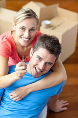 portrait of a joyful couple in their new house with woman showin