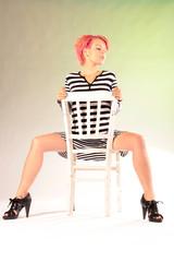 Frau sitzt mit gespreizten Beinen auf Stuhl