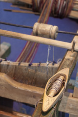 Closeup of vintage wooden weaving spindle on knitting loom