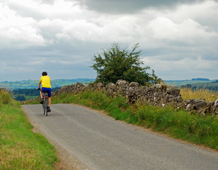 Cyclist on the brow of a hill on a country lane