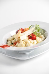Pasta served with cheese and nicely decorated in a white plate