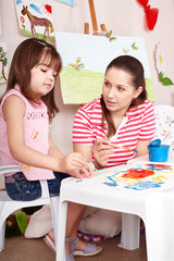 Child playing with teacher in preschool.