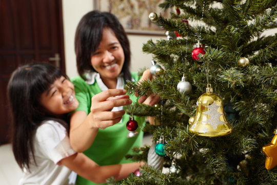 Asian mother and daughter decoarting Christmas tree