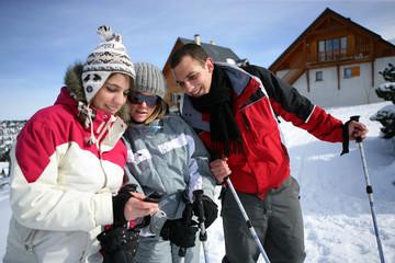Amis à la neige avec téléphone portable